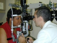 An ophthalmologist examines a patient's eye with a slit lamp.