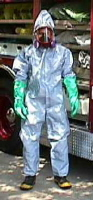 Rescuer wearing level C protection. The skin is protected the same as with level B, but the rescuer now is breathing filtered air from a powered air-purifying respirator (PAPR) rather than supplied air from a tank. Because it avoids the weight and complexity of a self-contained breathing apparatus (SCBA) system, Level C protection is much easier to wear and causes less heat stress. Level C protection is appropriate for most activities in the warm zone, unless droplet and/or vapor levels are very high. Photo credit: Tom Blackwell, MD.
