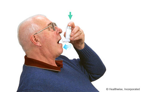 A man pressing on the inhaler and breathing in