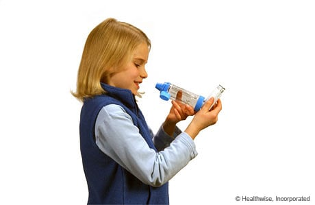 A child holding the inhaler upright