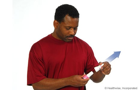 Picture of a man removing the cap from the inhaler