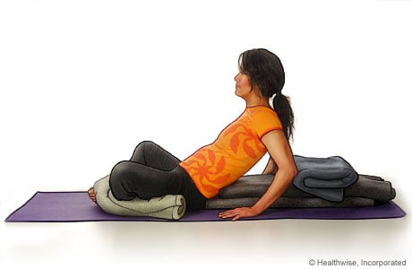 Picture of a woman in step six of reclining bound angle yoga pose