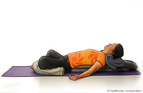 Picture of a woman in step seven of reclining bound angle yoga pose