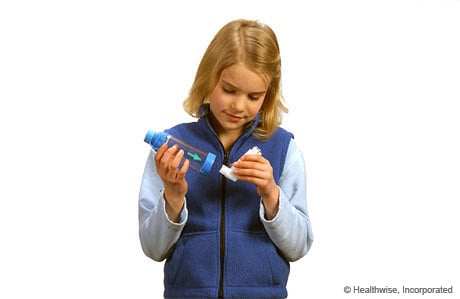 Photo of a girl putting the inhaler mouthpiece into the spacer