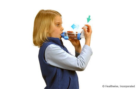 Photo of a girl pressing down on the inhaler and breathing in