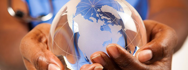 A person holding a small globe.
