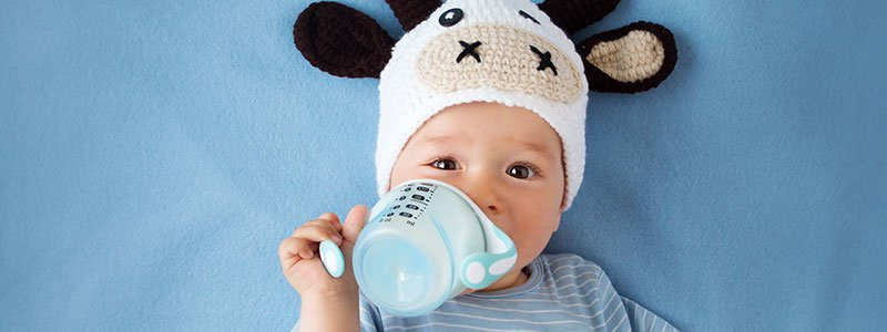 Baby drinking milk from bottle.