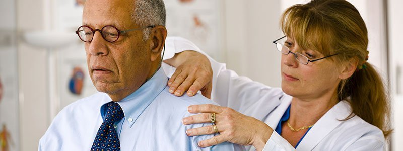 A doctor examining her patient's shoulder.