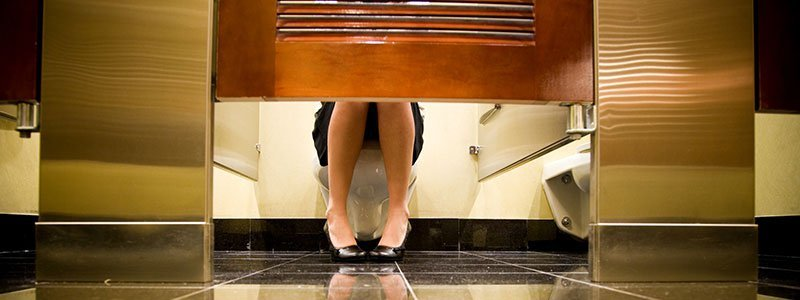 A woman sitting on the toilet in a public restroom stall.