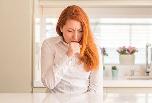 Picture of a woman coughing.