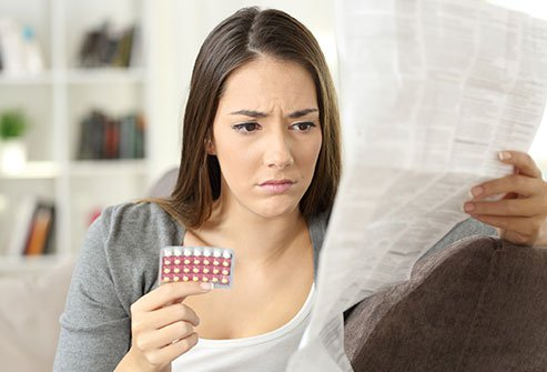 ALT Woman looking at a packet of birth control pills and instructions.