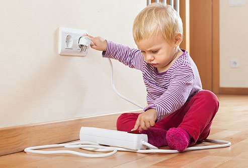 Image of a child playing with an electrical outlet.