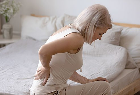 Picture of a woman holding her back in pain.