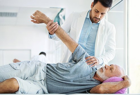 Picture of a healthcare professional examing a patien'ts shoulder.