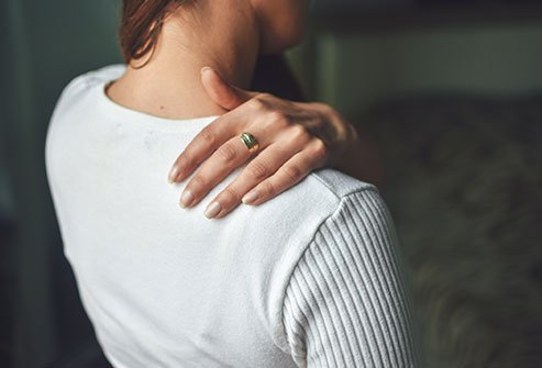 Picture of woman rubbing her shoulder.