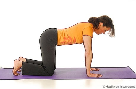 Picture of a woman in step one of yoga extended puppy pose