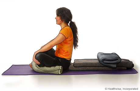 Picture of a woman in step four of reclining bound angle yoga pose