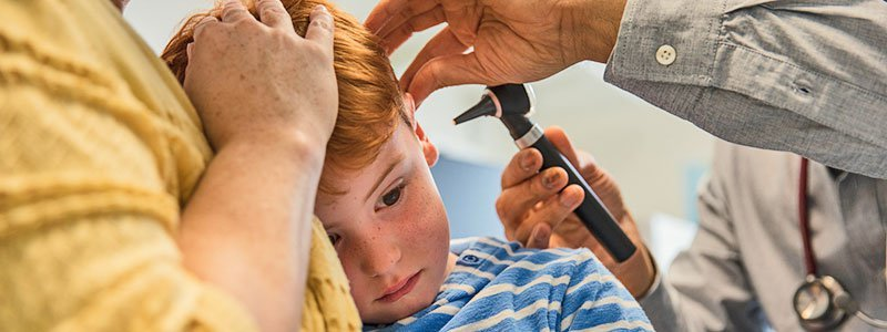 Doctor examines child's ear for infection.