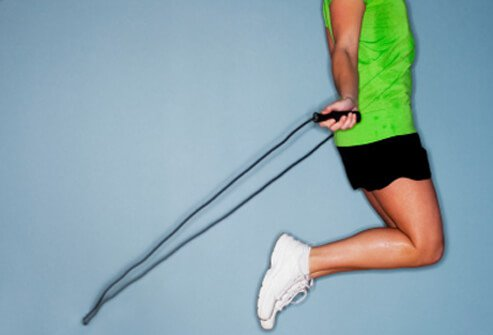 A woman exercises with a jump rope.