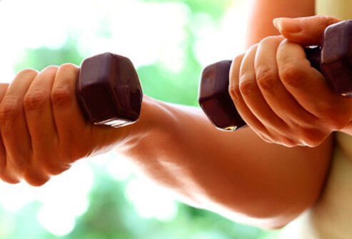 A woman uses hand weights to exercise.