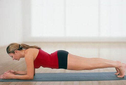 Lie face-down with your elbows directly under your shoulders, palms down and your toes tucked under.