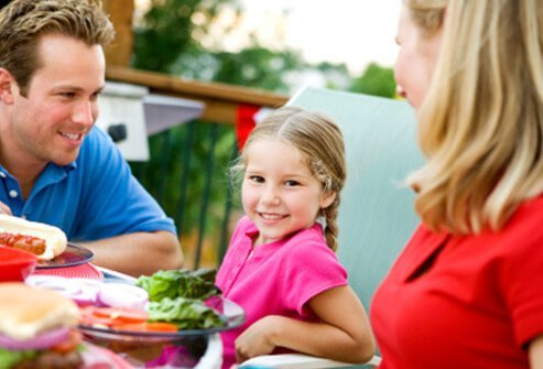 A girl eats a healthy lunch with her parents.