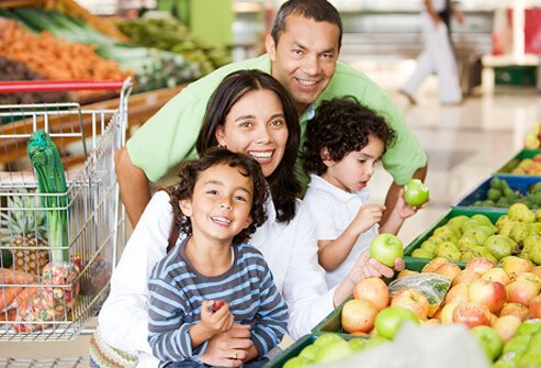 A family selects produce at the supermarket.