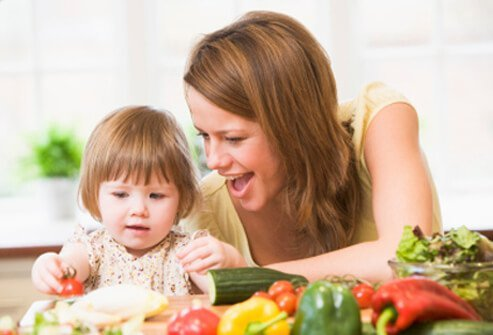 A mother feeds her daughter vegetables.