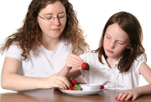 A mother and daughter share chocolate-dipped strawberries.