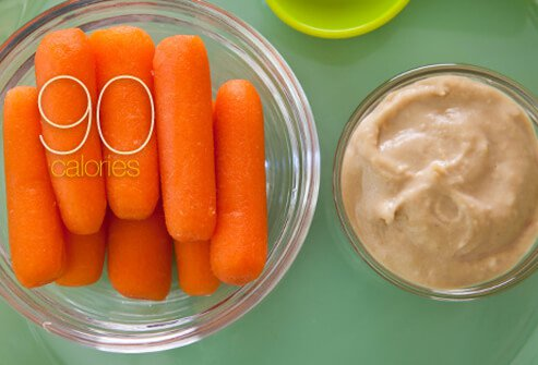 Baby carrots with a side of hummus dip.