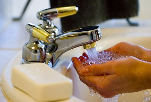 A person washes their hands in a bathroom sink.