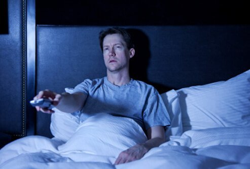 A man, unable to sleep, watches late-night TV.