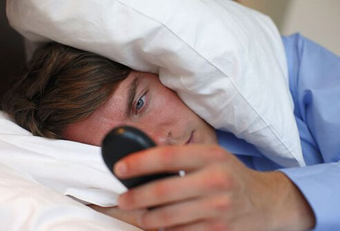 A man checks his cell phone in bed.