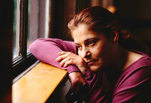 A women who is depressed staring out the window.
