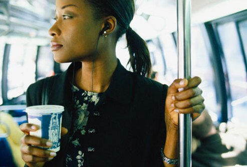 Woman holds a cup of coffee on a subway.
