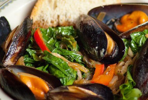 Photo of steamed mussels and greens.