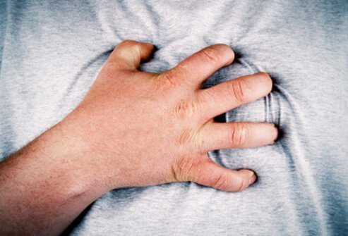 A man with indigestion pain grips his chest.