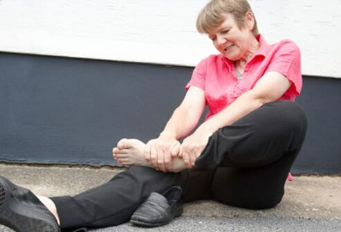 A woman is holding her swollen ankle.