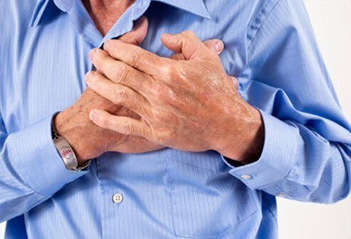 A man with chest pain clutches his chest. Chest pain is a symptom of a heart attack.