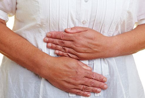 A woman suffers from nausea, a warning sign of heart attack or heart failure.
