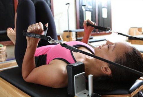 Photo of woman using reformer.