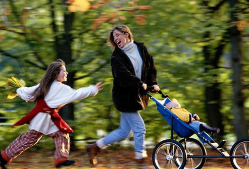 A woman getting some exercise while pushing her baby in a jogging stroller along side her daughter.