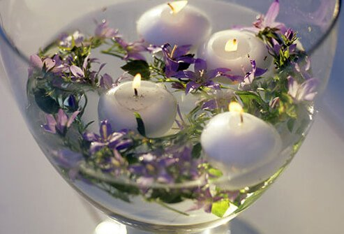 Scented floating candles and lavender in a glass vase.