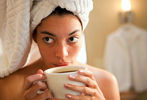 Photo of woman in towel drinking coffee.