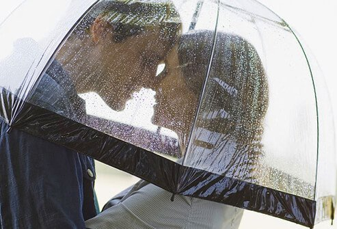A couple embracing under an umbrella.