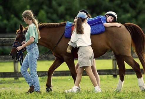 A boy with autism riding a horse and getting horse therapy