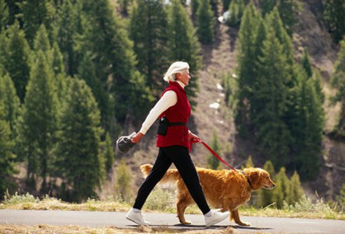A mature woman taking her dog for a walk