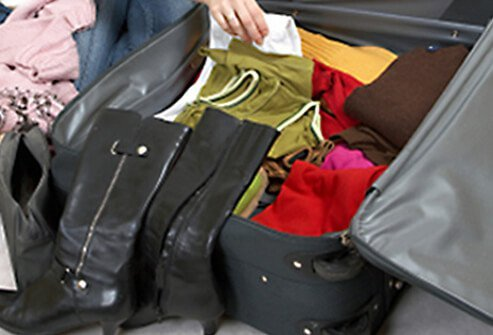 Woman deciding which clothes to pack in suitcase as well as what to keep with her.
