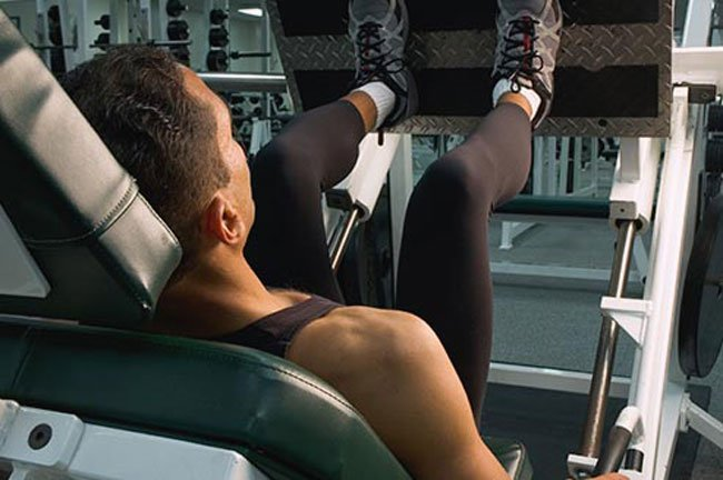 Sit on a leg-press machine with your back and head against the support and your feet flat on the foot plate.