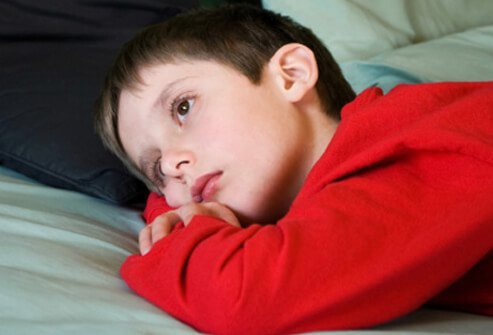 A boy feeling ill lies in his bed.